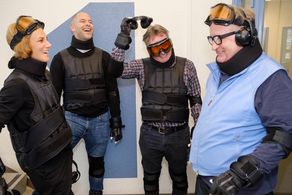 Eine Gruppe von Workshop-Teilnehmenden tragen alle einen Altersanzug. Sie sind daran, die Simulationsbrille abzulegen und tauschen sich in fröhlicher Stimmung aus.