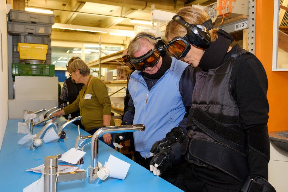 Workshop-Teilnehmende im Altersanzug ertasten verschiedene Armaturen für Bad und Küche.