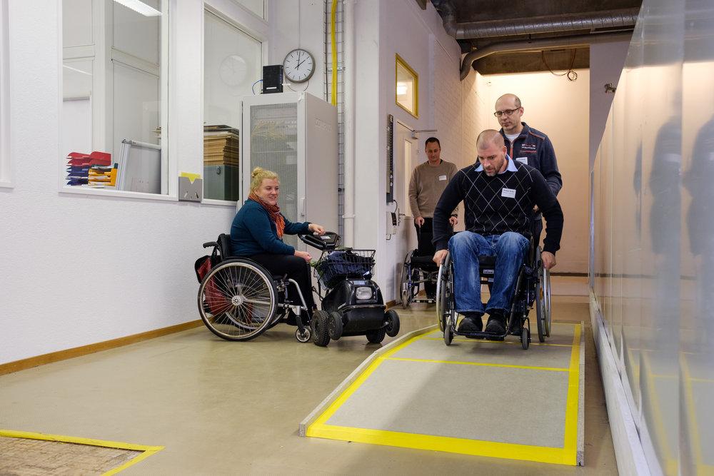 Ein Worshop-Teilnehmer im Rollstuhl fährt eine aufgebaute Rampe hoch und wird von seinem Kollegen hinten gesichert. Die Expertin im Rollstuhl schaut zu. Hinten wartet die nächste Gruppe auf die Übung.