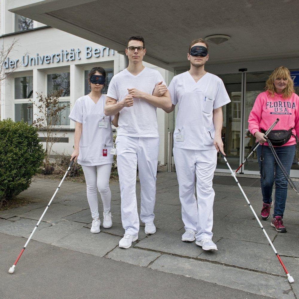 Drei Studierende der Zahnmedizin in weisser Kleidung, mit Dunkelbrille und Langstock ertasten sich den Weg aus der Klinik. Sie werden von einer Expertin mit Sehbehinderung begleitet.