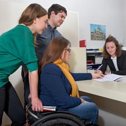 Gestellte Schaltersituation aus einem Fachkurs. Eine Rollstuhlfahrerin, eine Frau mit Sehbehinderung und ein Mann mit Hörbehinderung lassen sich von einer Kursteilnehmerin am Schalter auf Sitzhöhe beraten.