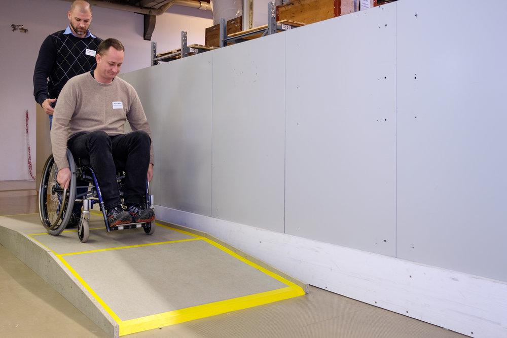 Ein Mann im Rollstuhl befindet sich auf der Plattform und schaut auf die kurze aber steile Rampe, die er gleich befahren wird.