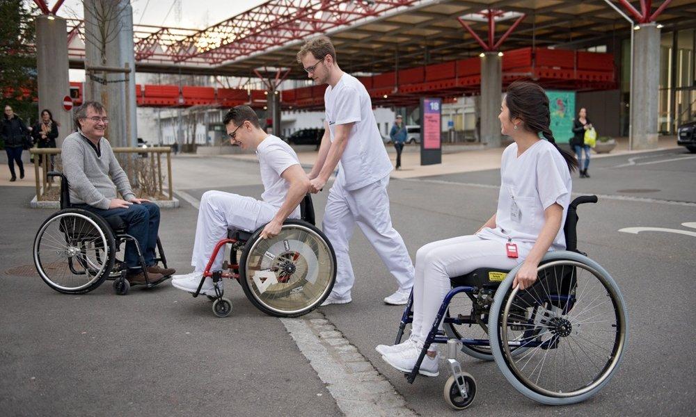 Ein Student der zmk im Rollstuhl überwindet lachend und mit Hilfe eines Mitstudierenden einen Trottoirrand. Eine Kollegin und der Experte - beide ebenfalls im Rollstuhl - schauen zu.