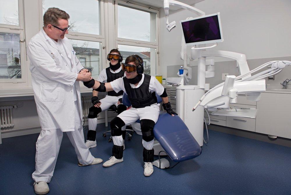 Praxisübung: Professor Schimmel hilft einem Studenten im Altersanzug beim Aufstehen aus dem Behandlungsstuhl.