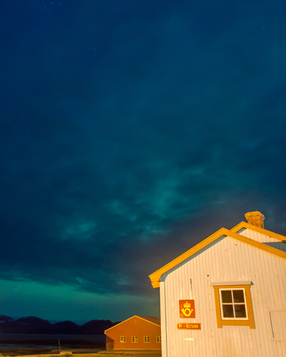 The post office in Ny-Ålesund, with aurora borealis in the background.