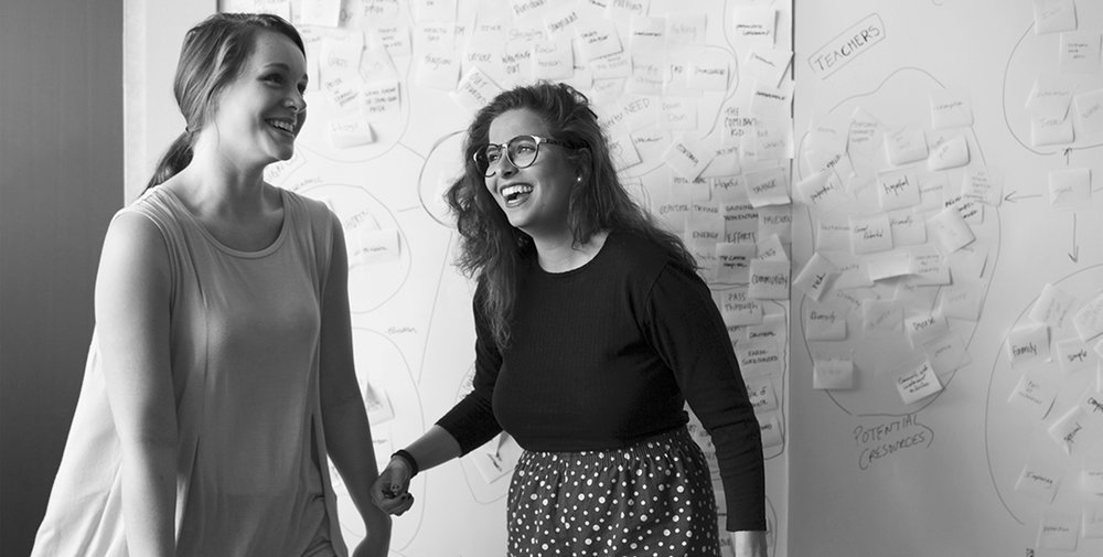 Two female design students laughing.