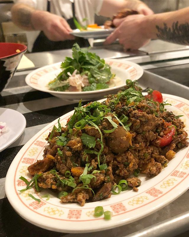 "Order up - Laap Muu Khua Phrae at #pokpoknw // Phrae-style spicy hand-minced pork ""salad"" with aromatics, spices, herbs, cherry tomatoes, cracklings and crispy fried garlic.  Served with phak sot."