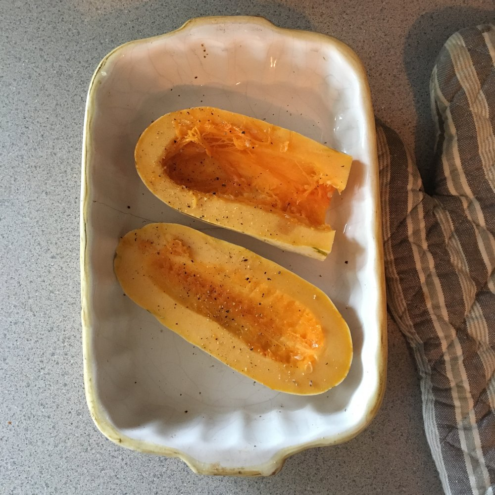 Preparing the squash for roasting. It's easier to peel if you roast it, let it cool and then take a paring knife to peel off the skin. Delicata squash also has a thinner skin than an acorn squash so roasting time might differ slightly.