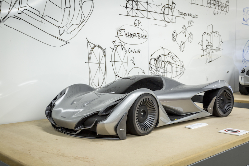 A clay model of a silver concept car inside the Art Center Design Studio.