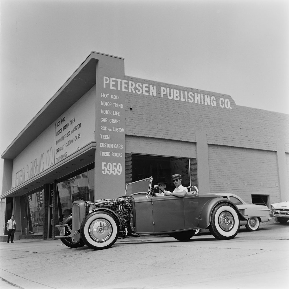 A man in a hot rod outside of the old Petersen Publishing Company building.