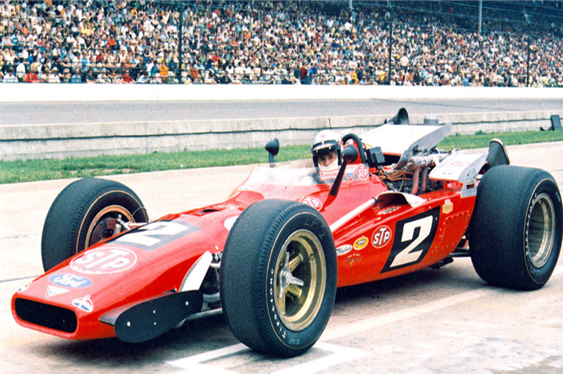 Mario Andretti sitting in an indycar on the side of a race track.