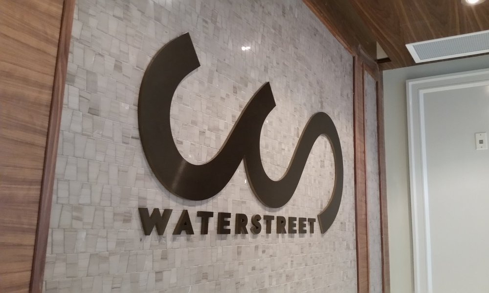 Brushed bronze laser cut logo, mounted to marble tile.