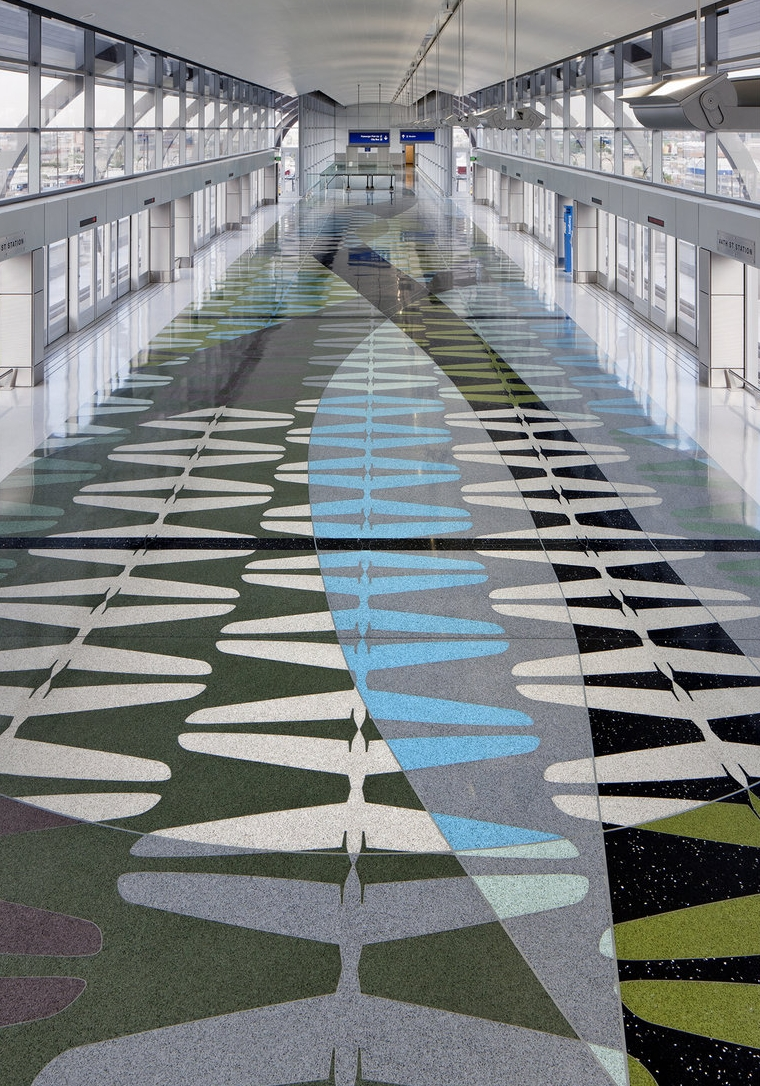 Phoenix Sky Harbor Airport Train Station / Phoenix Arizona The floor is inspired by the outline of an airplane's horizontal stabilizer, known as a tailplane. Fernandez used ten colors to create the platform's rhythmic geometric patterns and sweeping bands. He heightened the floor's reflective qualities by adding aggregates of recycled, crushed glass and mirror.