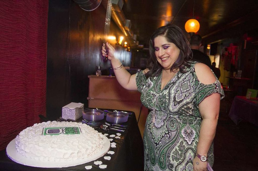 Laura Garza, executive artistic director of Teatro Audaz, cuts cake at The Pachanga held in celebration of the company's first season in residence at The Playhouse San Antonio.