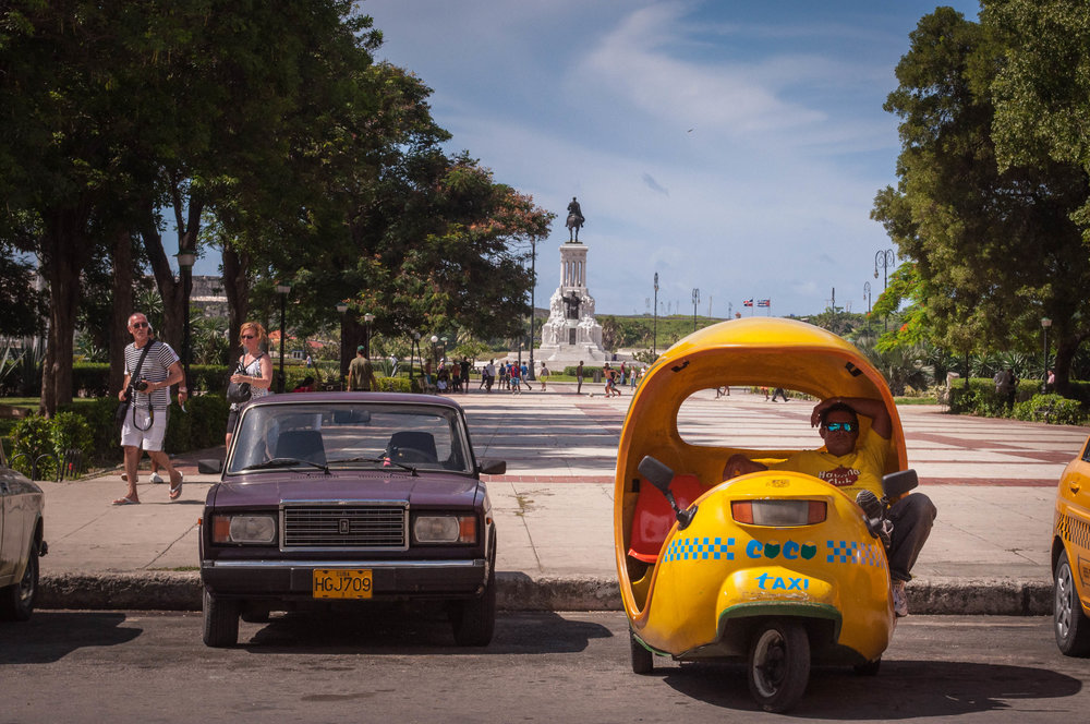 Coco taxi with a driver resting on the vehicle next to an old car with a large public square behind. Photo taken during the our day trip to La Havana