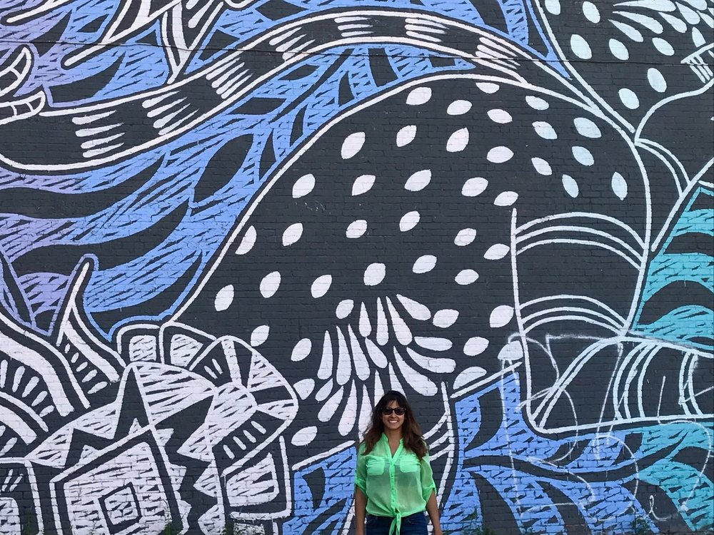 Latino women in a green shirt in front of a giant blue mural with black invented animals in Montreal (Canada)