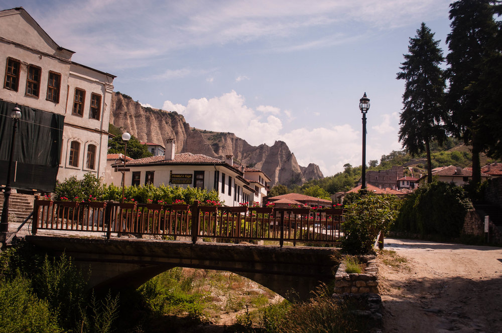 Town of Melnik with its traditional white house architecture and the rock pyramids on the background. On the foreground there is a bridge. This is a stop in our road trip Bulgaria