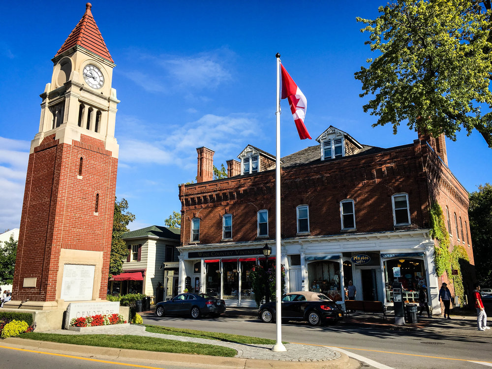 Niagara on the Lake town with a clock tower, the canadian flag and a victorian building