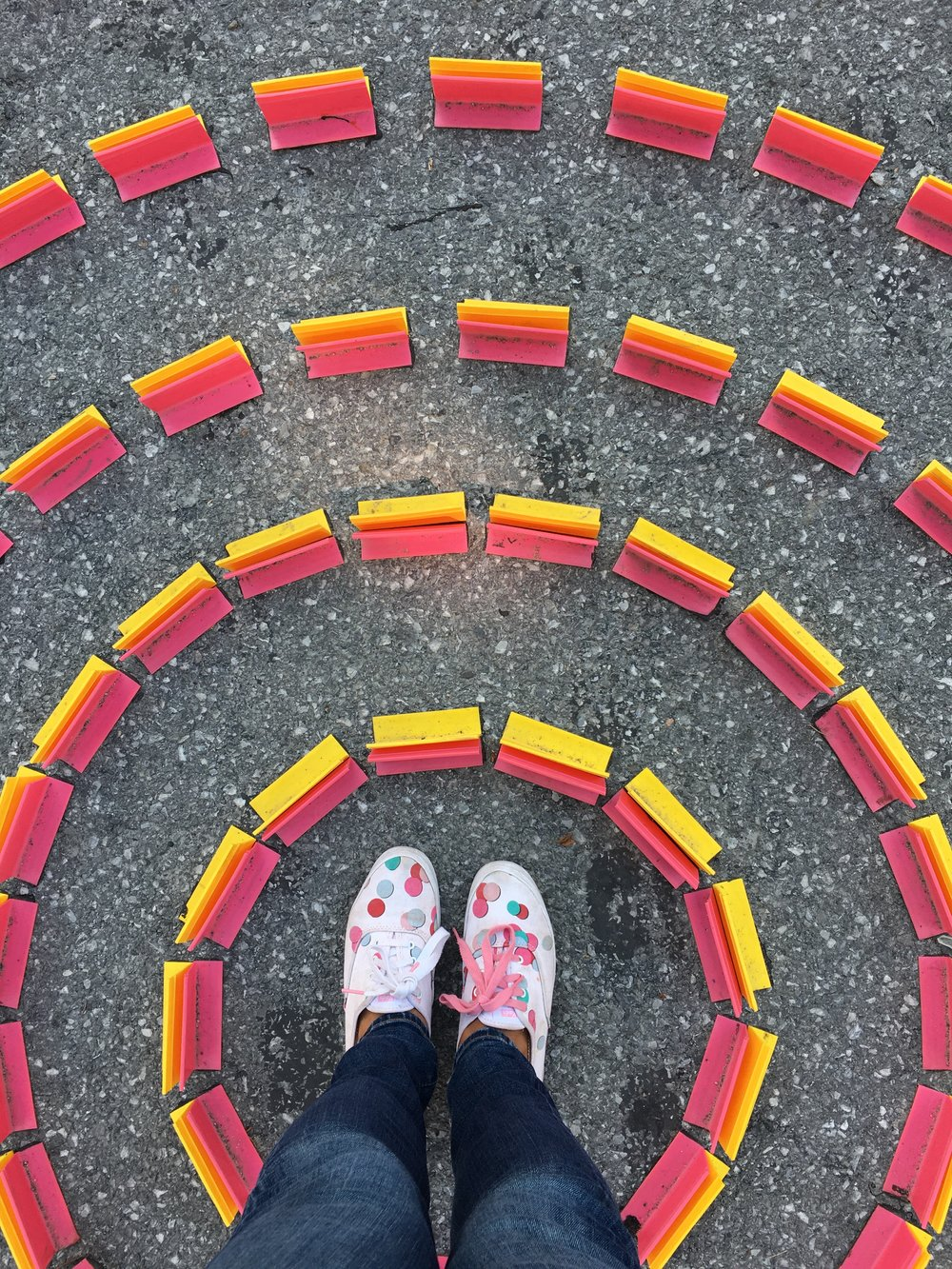 Feet with white, pink & green Keds shoes in the middle of a street art installation in Montreal with pink and yellow circles expanding. Work with me page of the BRB Travel Blog