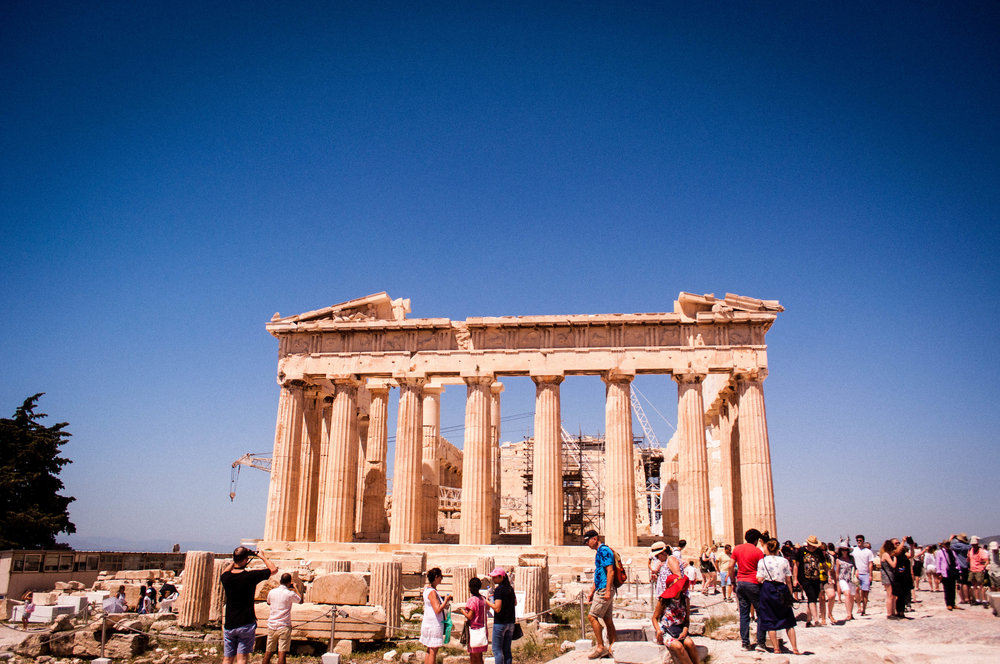 "Parthenon in Athens Greece filled with tourists with a blue sky on the backdrop. This image is a good representation for the article ""how to avoid tourists in Greece"""