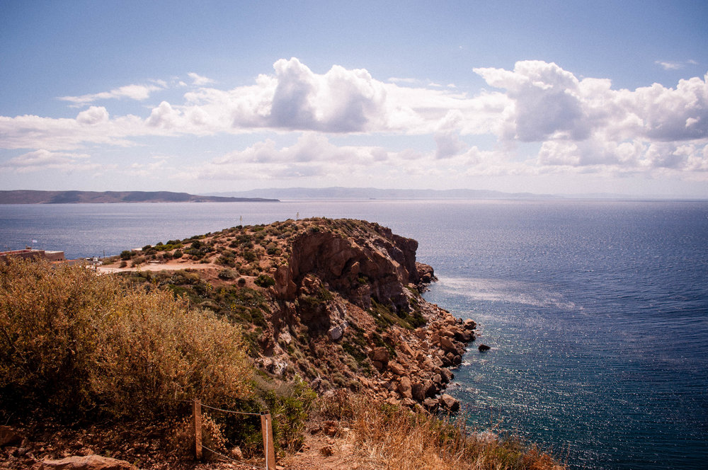 Blue sky with clouds, sea and creeks with desert-like vegetation in Sounion (Greece)