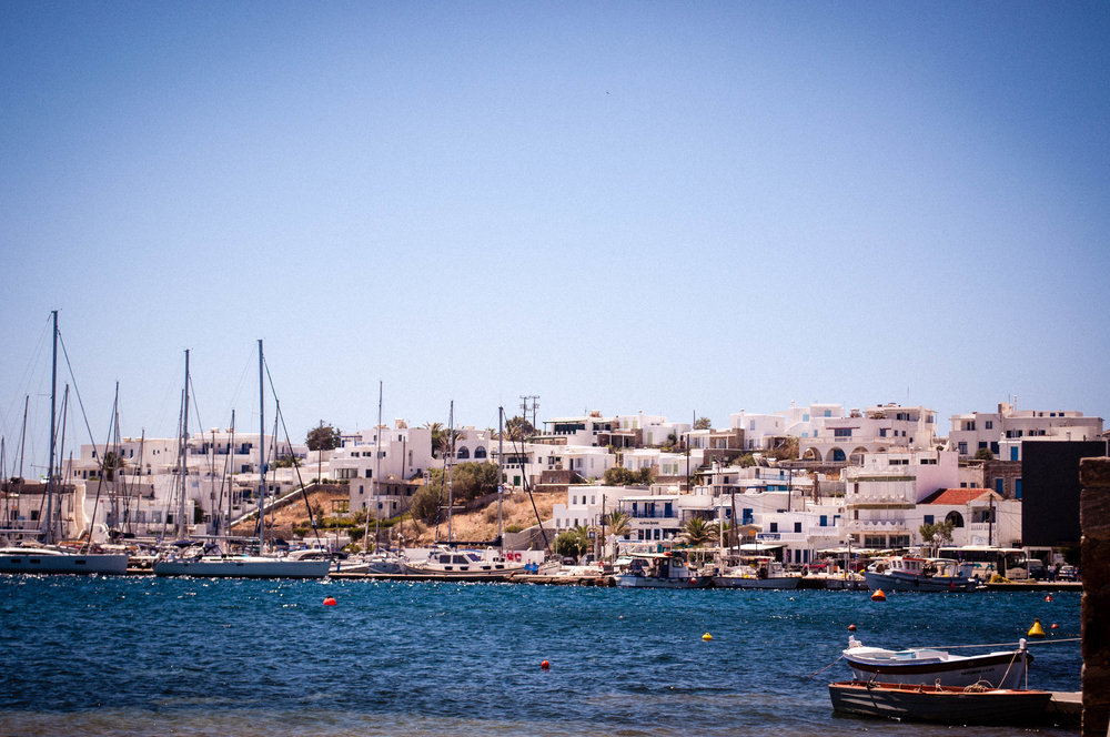 Port of Serifos with boats, the blue see and on the background its traditional architecture of white buildings