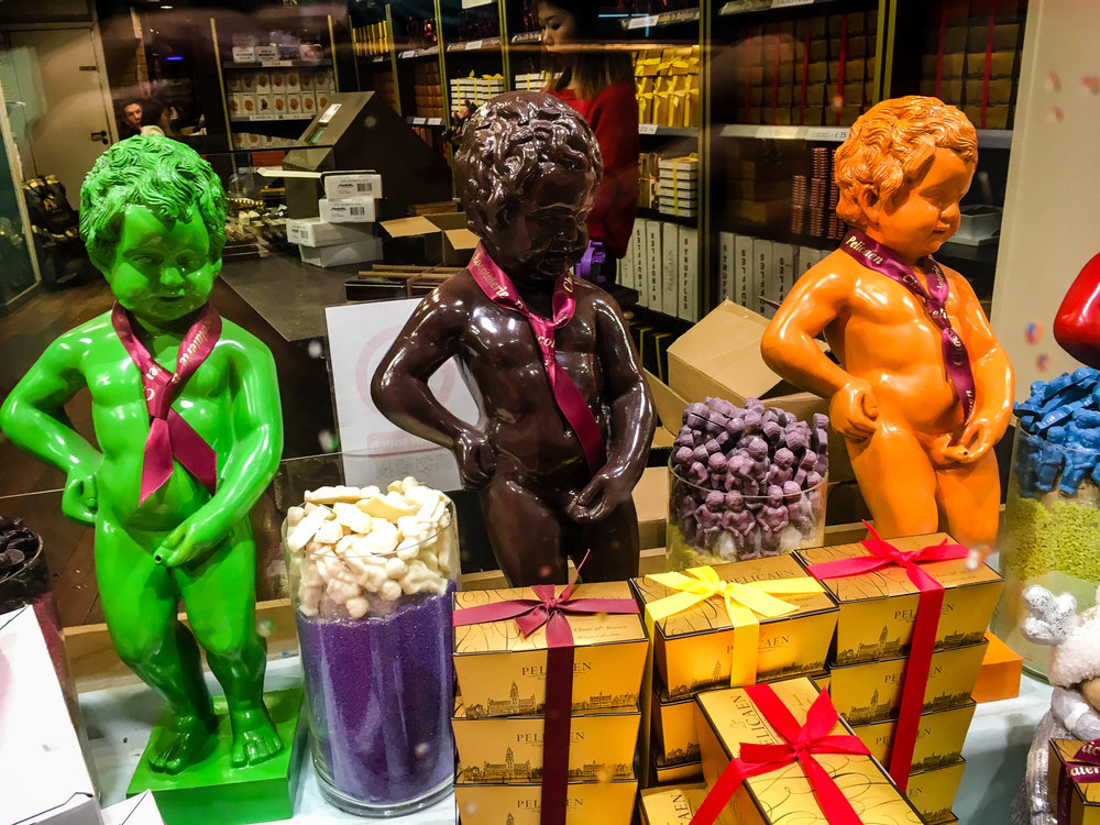 Several Manneken Pis made of chocolate with very bright neon colours on a chocolate shop window seen during our Brussels Beer and Chocolate Tour given by Brussels Journey