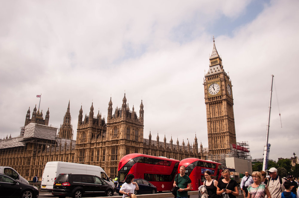Big ben and red double decker buses in London. This landmark can be seeing during a long layover in London (UK). Sightseeing in 8 hour layover in London