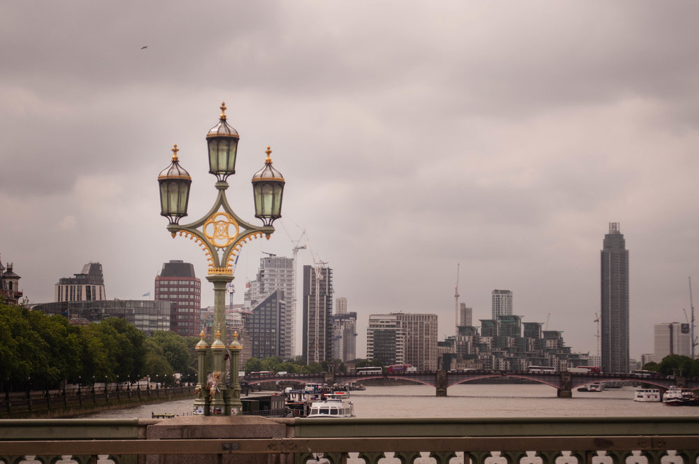 Bridge in London with a gold and green lamp post with skyscraper buildings in the background. This landmark can be seeing during a long layover in London (UK)