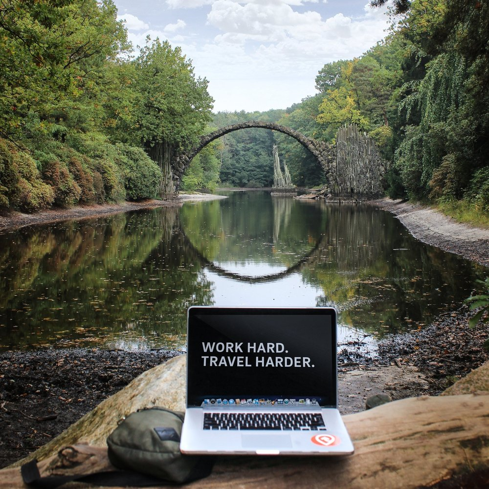 Computer near a bridge with the sentence work hard. Travel Harder. It was used as an illustration to ask your boss for vacations in 3 simple steps.