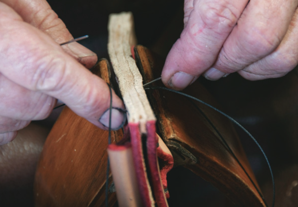 Using two needles to stitch sheath pieces and spacer held in saddler's vice.