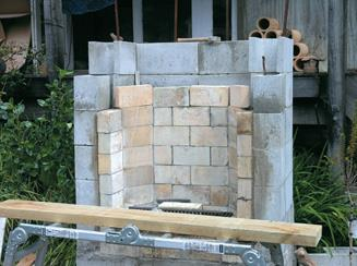 Fireplace hearth with scoria-cement mix layer between bricks and outer wall