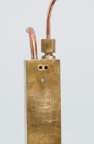 Brass stand with steam inlet and outlet.