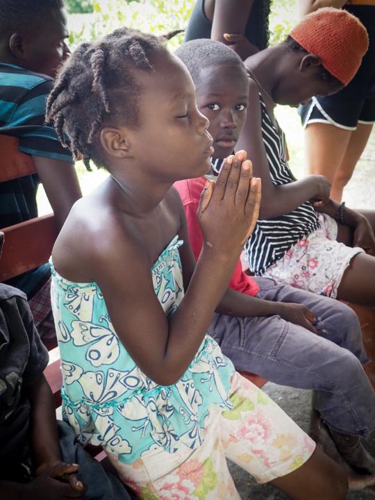 Whitney praying during VBS, Petite Riviere De L'Artibonite
