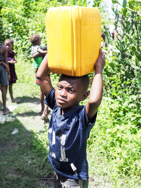 Little boy carrying water