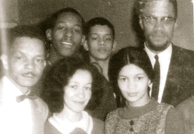 Left to right: Tom Wallace Sr., Rodnell Collins, Tom Wallace Jr., Malcolm X. Front Row: Mrs.Wallace and Daughter Gail, February 21, 1965