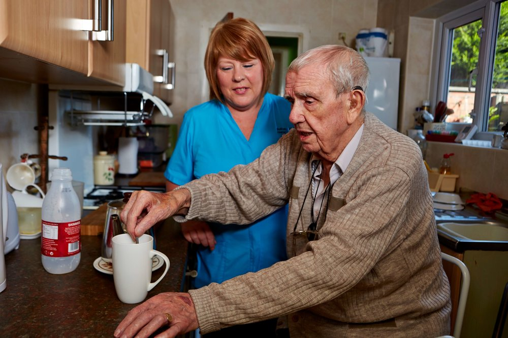Image of an elderly man receiving support at home from a healthcare professional