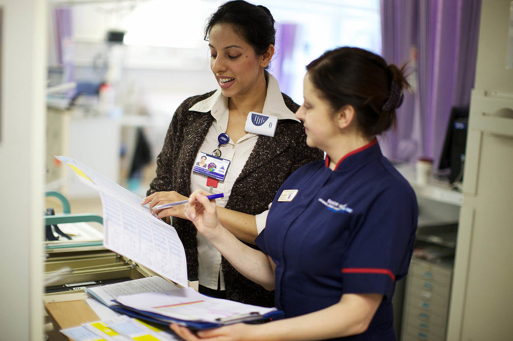 Image of two healthcare professionals discussing a case file