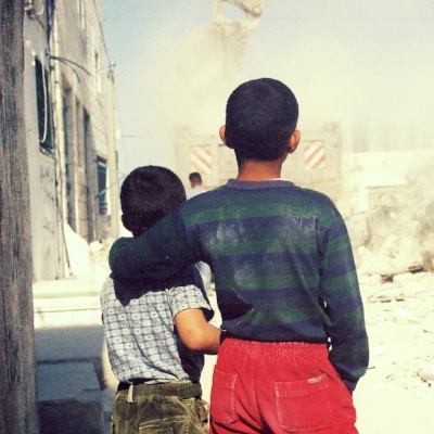 image: 2 Palestinian children watching their house demolished by the Israeli Military taken by Eric Fistler, Dheisheh Refugee Camp in Bethlehem 2004