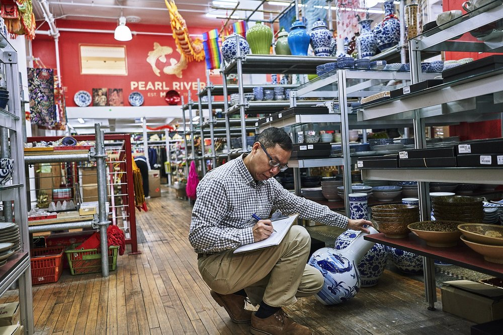Wilkie Wong checks the price of a ceramic vase. One of Pearl River's longest serving employees, Wilkie started working at the store as a high school student and stayed for 36 years, rising to Vice President.