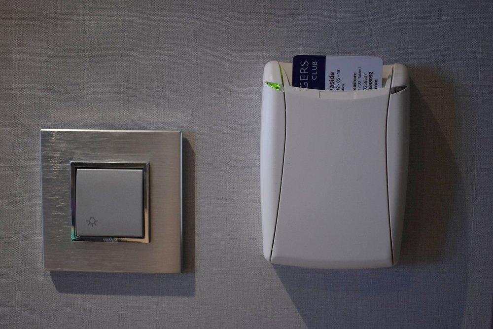 No quarto, perto da porta há esse suporte para colocar o cartão de embarque e ativar a energia do quarto