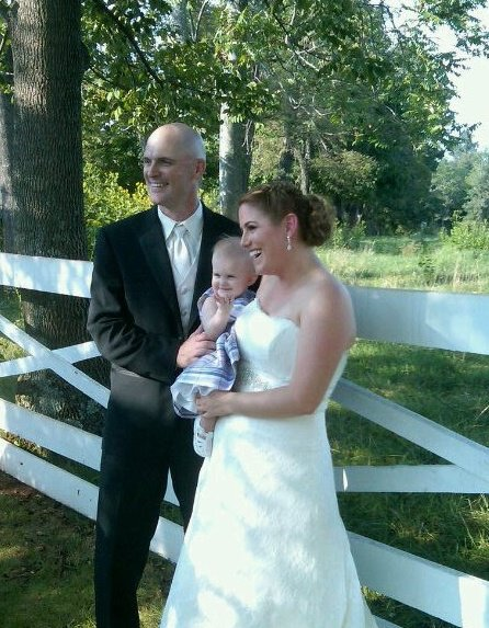 nikki and husband at their wedding holding baby molly