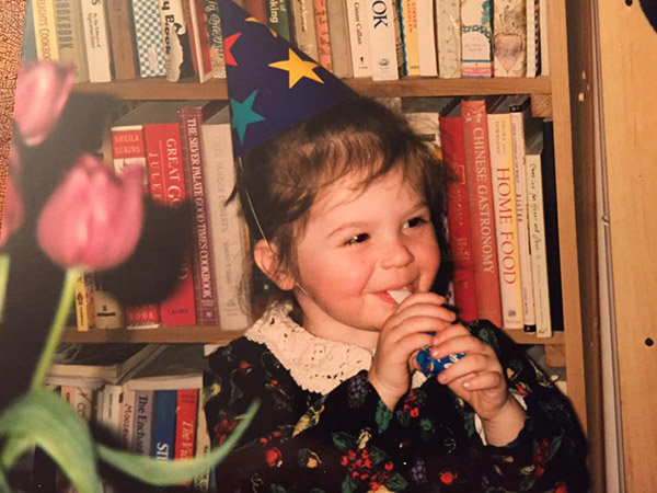 Oona at age two-cookbook collection as backdrop.
