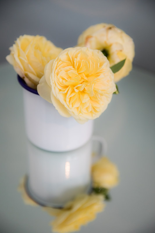 Yellow flowers in vase on mirrored table