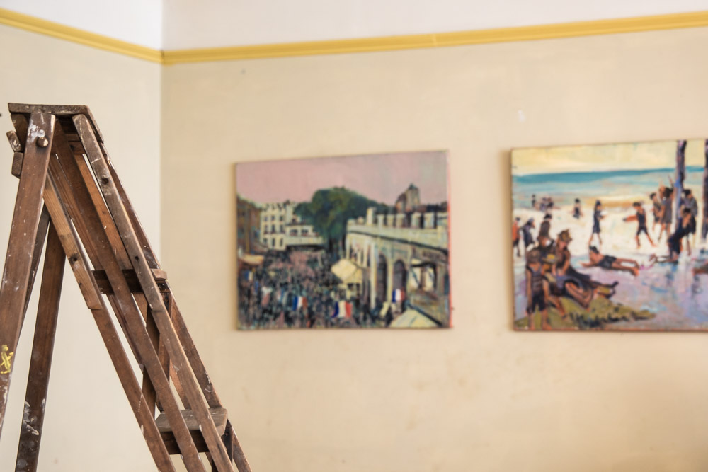 Ladder and paintings yellow picture rail
