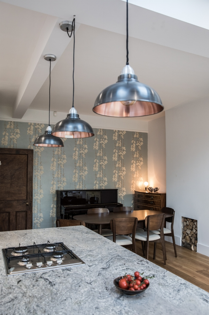 Three Old Factory Pendants in Nancy's kitchen. I love the way one is hooked into position across the beam. Lovely little detail!