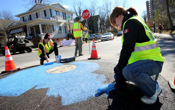 Bonnie Adams (right) with Travel with Care and Rachel Schaffner, project coordinator for Fayetteville's Sustainability Department, paint the interior of a new mini-roundabout Thursday at Spring Street and School Avenue. The mini-roundabout is a pilot project to exemplify the concept of tactical urbanism. The project is similar to the temporary crosswalk in front of the Walton Arts Center's Nadine Baum Studios.
