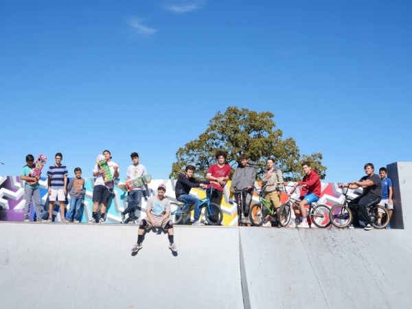 Visual artist Graham Edwards (seated) is joined by local skaters and BMXers in front of Edwards' colorful geometric designs.