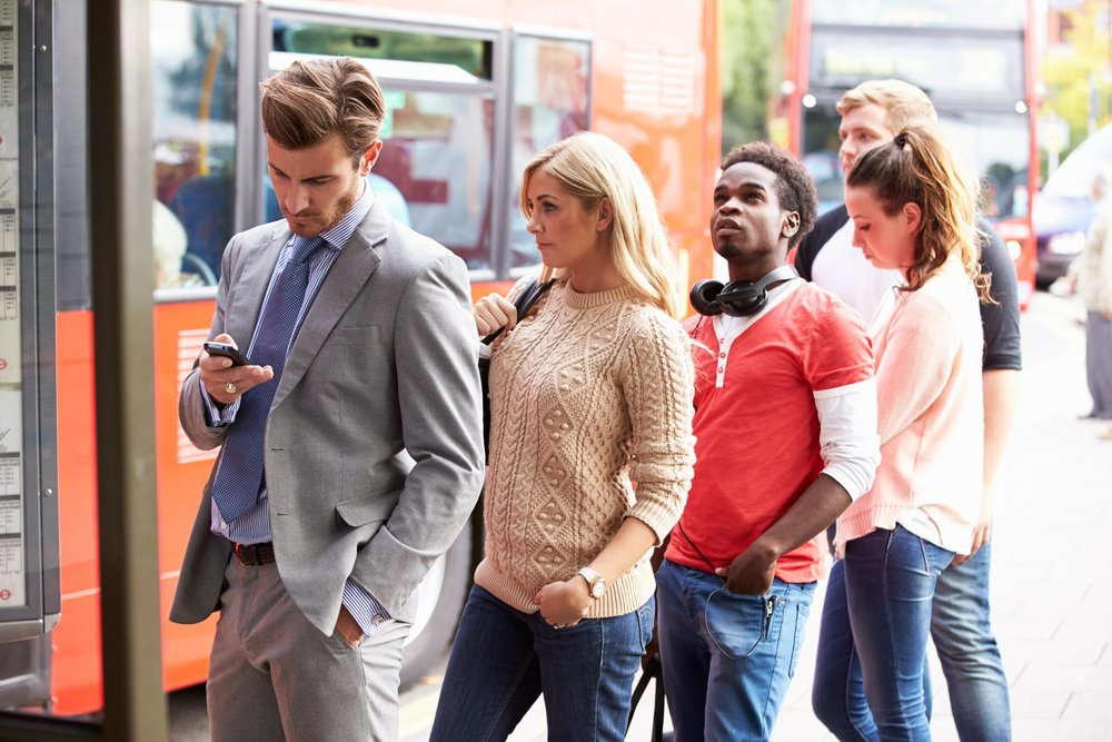 diverse-group-of-people-waiting-at-a-city-bus-stop-on-phones-and-looking-around.jpg