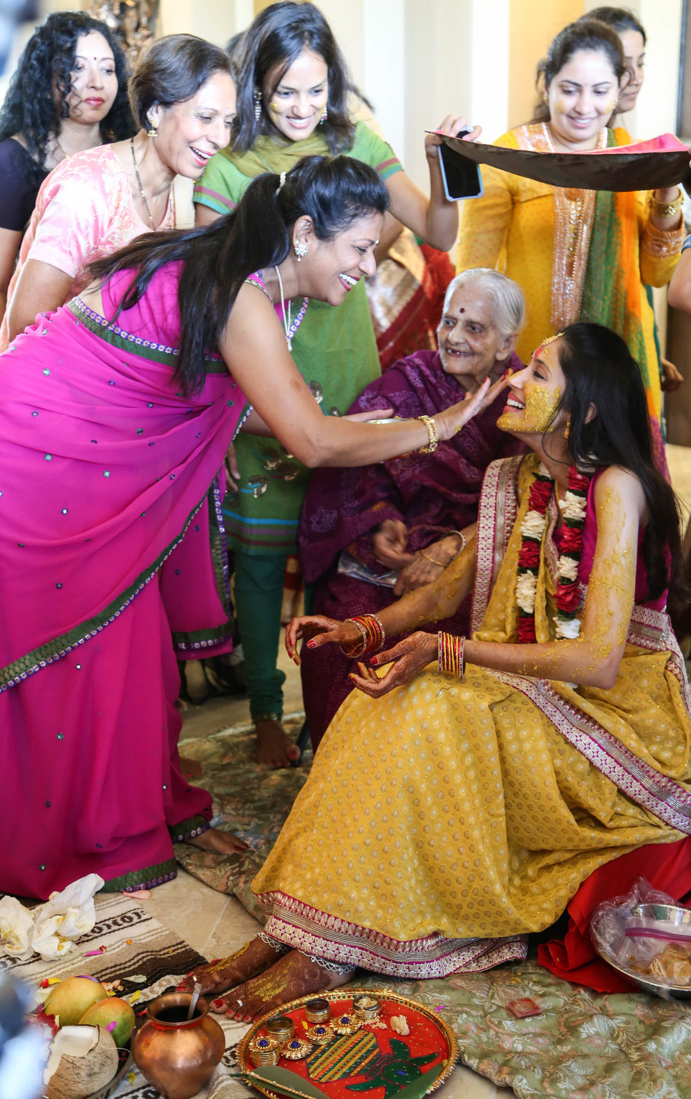 Pithi ceremony where one of the Aunties is applying Haldi on the bride.